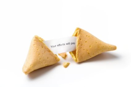"""a broken fortune cookie isolated on white with message """"your efforts will pay"""""""